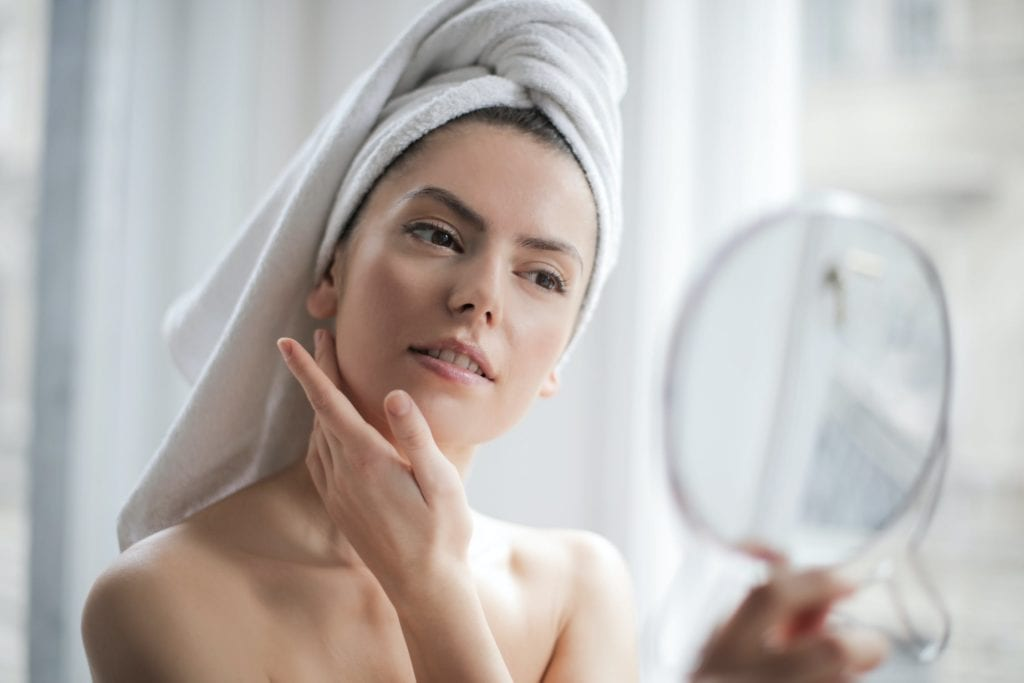 A woman with a towel on her head looks into a mirror
